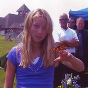 A young girl holding a monarch butterfly during a butterfly release at a funeral in York, PA