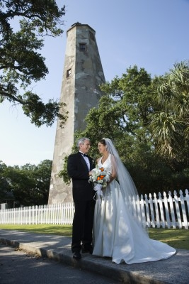A handsome wedding couple takes photos in front of the Bald Head Island Lighthouse.